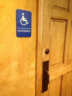 Photo of a blue Handicapped Accessible sign next to a door.