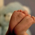 A close of of tiny baby feet with a teddy bear in the background