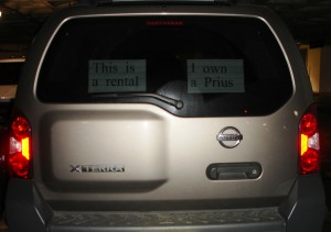 "Nissan Xterra SUV with a sign in the window saying ""This is a rental; I own a Prius""."