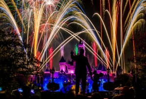 """Dreams Come True"" fireworks display over the Sleeping Beauty Castle at Disneyland with Walt and Mickey's statue in front."
