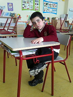 A bored-looking student sitting at his desk.